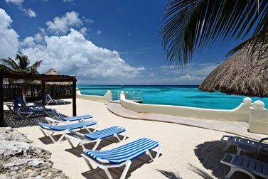 lounge chairs in the sandy area of this Cozumel vacation rental condo